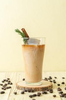 Gieten melk in zwarte koffie glas met ijsblokje, kaneel en rozemarijn op hout achtergrond