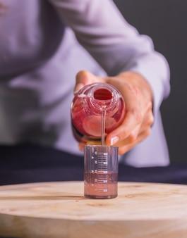 Gieten rode vloeistof in bekerglas op snijplank