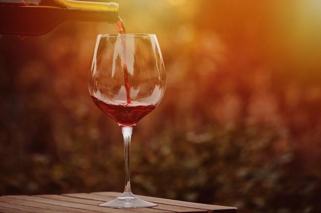 Gieten rode wijn in het glas.