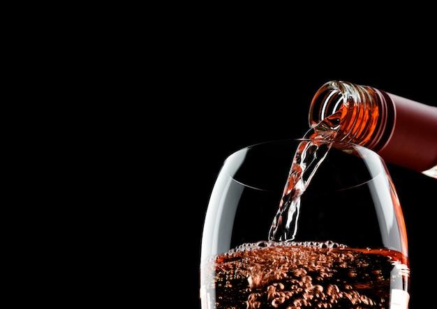 Gieten roze rose wijn van fles tot glas geïsoleerd