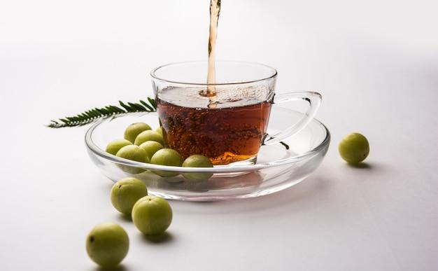 Gieten van amla thee of avla chai in transparante glazen kop met schotel over witte of zwarte achtergrond. populaire ayurvedische geneeskunde uit india