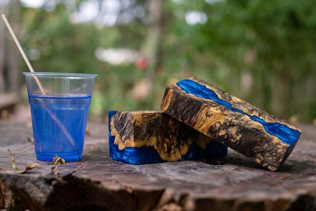 Gieten van blauwe epoxyhars wortelnotenhout kubus op oude tafel