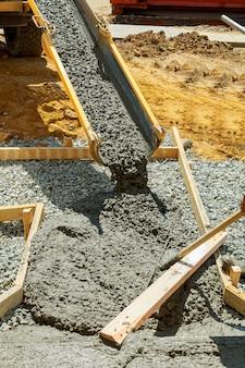 Gieten van cement voor de bestrating van het huis naar de weg