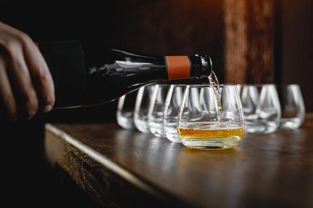 Gieten van cider in glas uit de fles