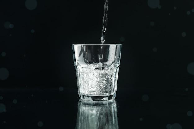 Gieten van gezuiverd zoet water in glas op spiegel