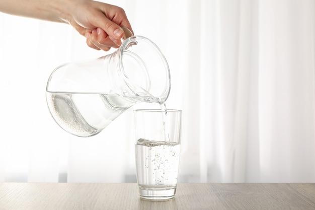 Gieten van gezuiverd zoet water uit de kruik in glas op houten tafel