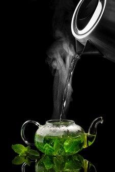 Gieten van heet water in een glazen theepot op een zwarte tafel, muntthee