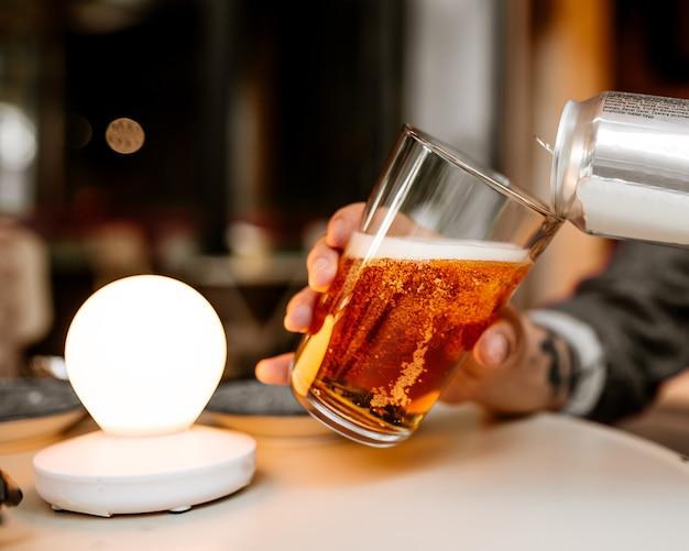 Gieten van vers koud bier in een glas uit een blikje
