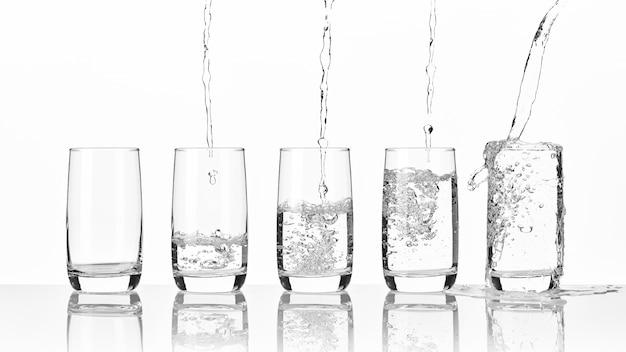 Gieten van vers mineraalwater in vijf glazen staande op een glazen tafel op een lichte muur