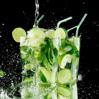 Gieten van verse mojito cocktail in glazen geïsoleerd op zwarte achtergrond