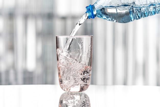 Gieten van water uit blauwe fles in glas