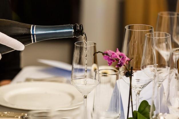 Gieten witte wijn uit fles in het wijnglas op de tafel over onscherpe achtergrond