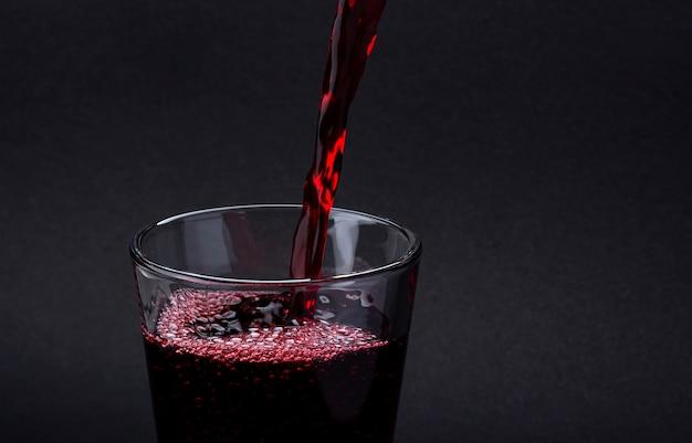 Gietend coladrank op een glas