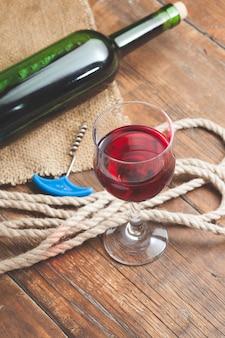 Gietend rode wijnglas tegen houten lijst