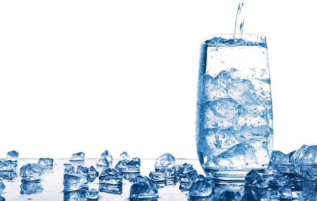 Gietend water in glas met ijs dat op witte ruimte wordt geïsoleerd