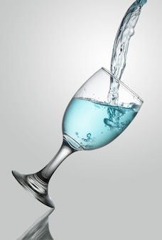 Gietend water op champangeglas op witte achtergrond