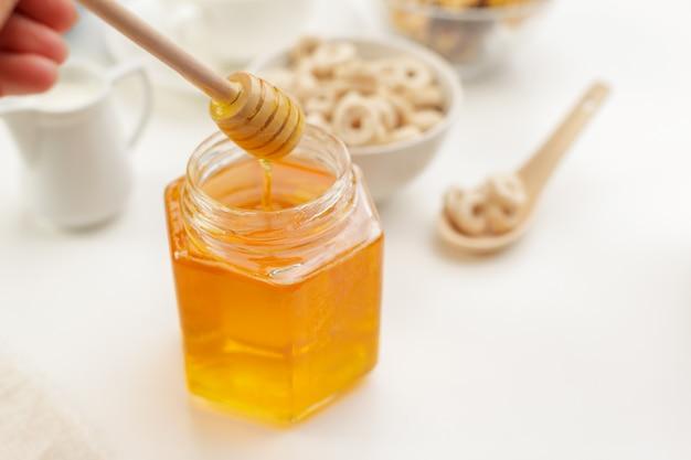 Gietende aromatische honing in kruik, close-up