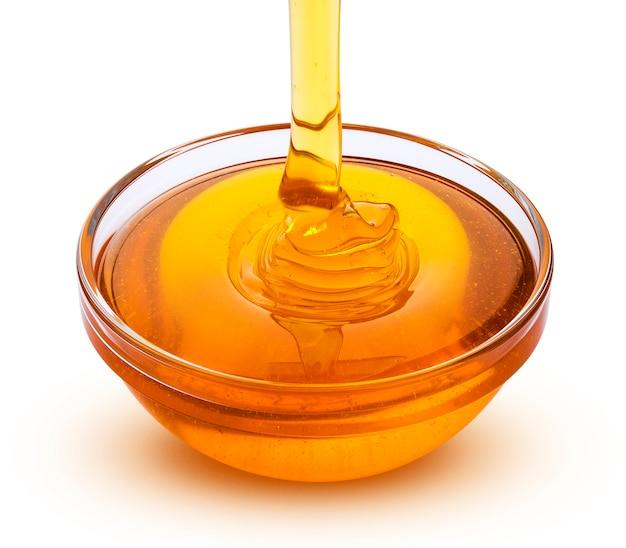 Gietende honing die op wit wordt geïsoleerd