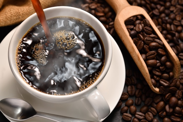 Gietende koffie met rook op een kop en koffiebonen op jutezak op zwarte achtergrond