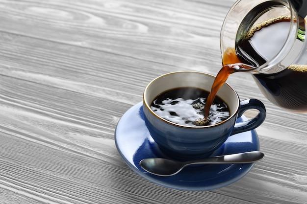 Gietende koffie met rook op een kop op houten achtergrond