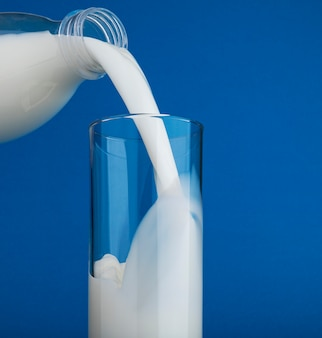 Gietende melk in glas dat op blauwe achtergrond wordt geïsoleerd