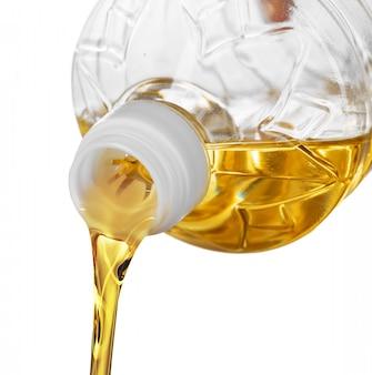 Gietende olie voor het koken in een fles die op wit wordt geïsoleerd