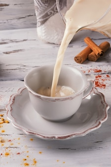 Gietende traditionele indische hete thee met kruiden