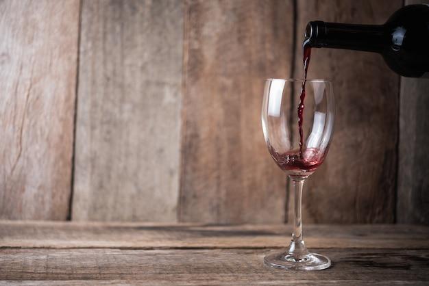 Gietende wijn in glas op houten achtergrond
