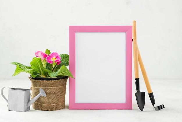 Gieter en hulpmiddelen naast bloemenhulpmiddel