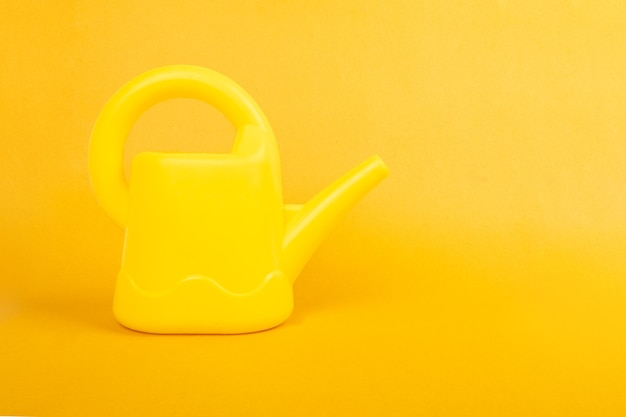 Gieter op gele achtergrond met kopie ruimte.