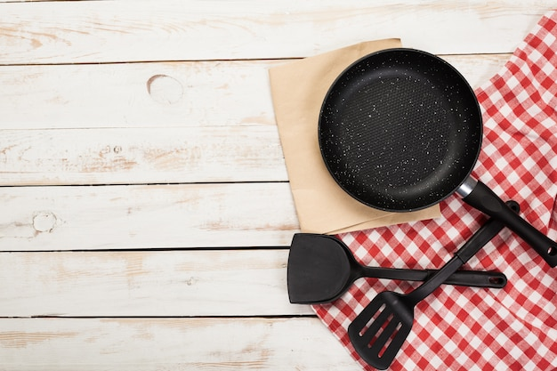 Gietijzer pan en ander keukengerei op houten tafel, bovenaanzicht