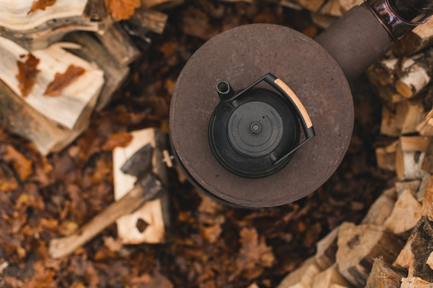 Gietijzeren ketel voor traditionele oosterse theeceremonie op verbrand fornuis met prachtige herfst eikenbladeren en gestapelde boomstammen op de achtergrond
