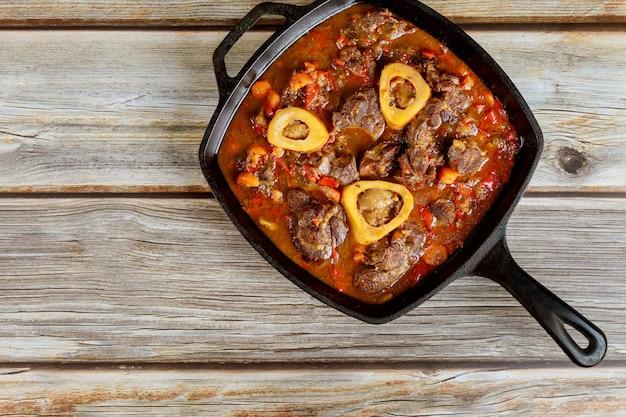 Gietijzeren pan met ossobuco gemaakt van rundersteel en groente.