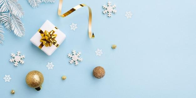 Gift boog met gouden kerstversiering op blauwe achtergrond