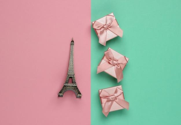Gift boxex met strik, beeldje van de eiffeltoren op roze blauwe pastel achtergrond. winkelen in parijs, souvenirs. bovenaanzicht