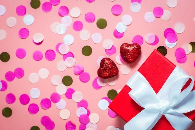 Gift en rode glanzende harten op een roze tafel. plat lag, bovenaanzicht.