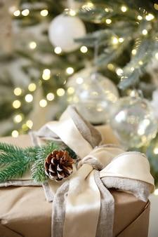 Gift in doos op achtergrond van kerstmisslinger en nieuwe jaarboom