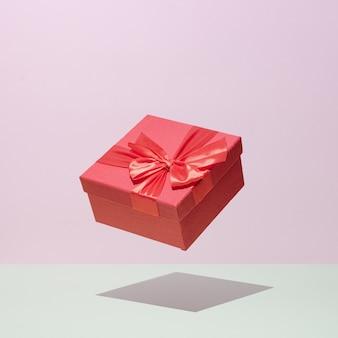 Gift in een rode doos in levitatie op een pastel achtergrond bruiloft feest gefeliciteerd concept.