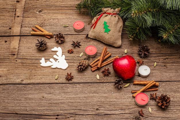 Gift in zak, nieuwjaarsboom, appel, kaarsen, kruiden, herten, kegels. natuurdecoraties, vintage houten planken