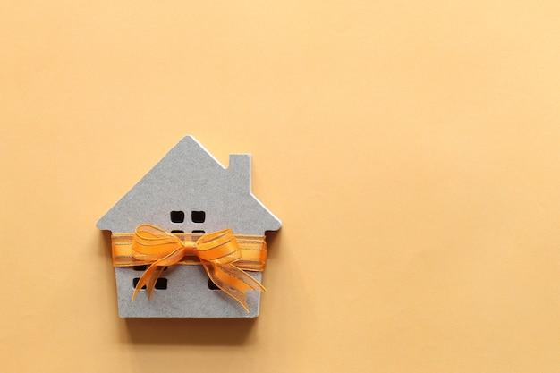 Gift nieuw huis en onroerend goed concept, model huis met oranje lint als geschenk