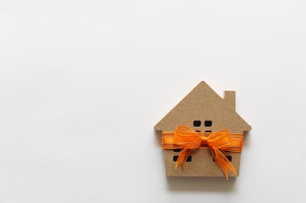 Gift nieuw huis en onroerende goederenconcept, modelhuis met oranje lint op wtiteachtergrond