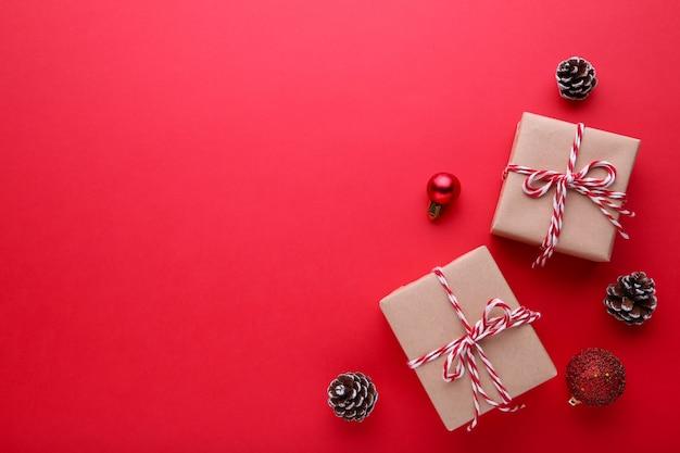 Gift presenteert doos met kerst decor op een rode achtergrond.
