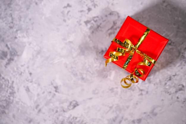 Gift, rode doos die op een grijze achtergrond, close-up wordt ingepakt. vakantie, nieuwjaar, kerstmis. platliggend, verrassend bovenaanzicht