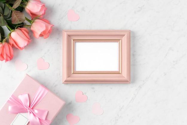 Giftbox en roze roze bloem op marmeren witte tafelachtergrond voor valentijnsdag vakantie groet ontwerpconcept.