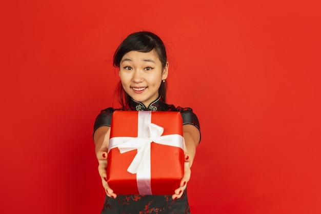 Giftbox geven. gelukkig chinees nieuwjaar 2020. het portret van het aziatische jonge meisje dat op rode achtergrond wordt geïsoleerd. vrouwelijk model in traditionele kleding ziet er gelukkig uit. viering, vakantie, emoties. copyspace.