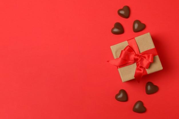 Giftdoos en chocoladeharten op rode achtergrond