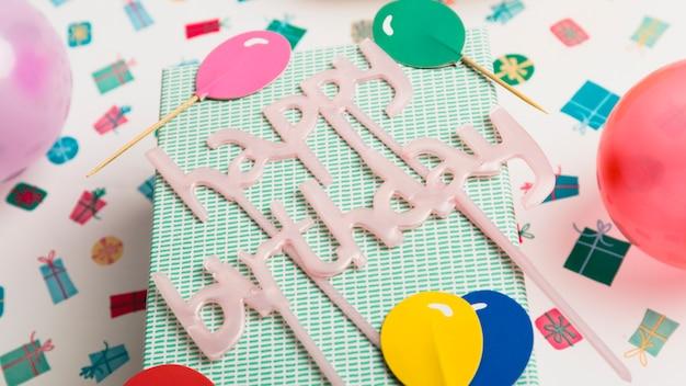 Giftdoos en gelukkig verjaardagsteken tussen ornament en heldere ballons