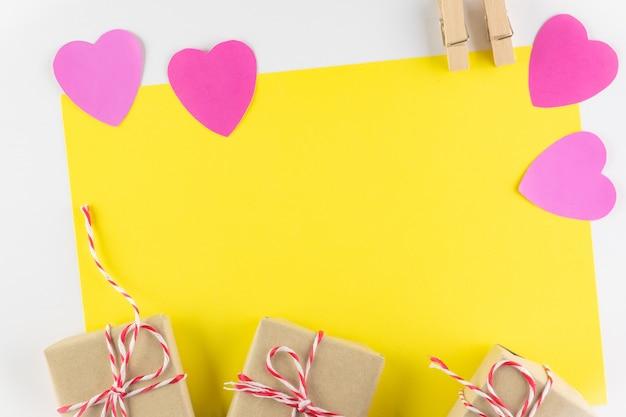 Giftdoos en roze liefdeharten op gele achtergrond, de dag van de gelukkige valentijnskaart