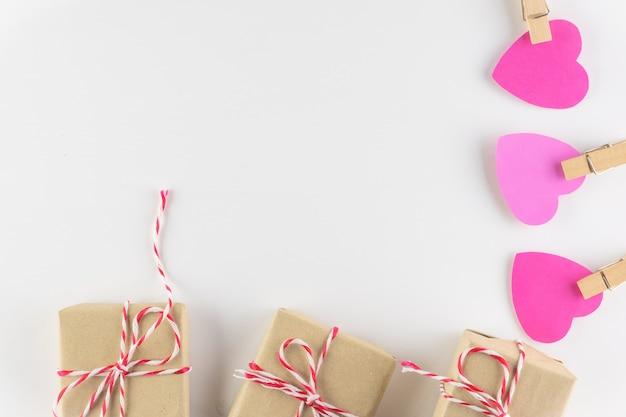 Giftdoos en roze liefdeharten op witte houten achtergrond, de dag van de gelukkige valentijnskaart.