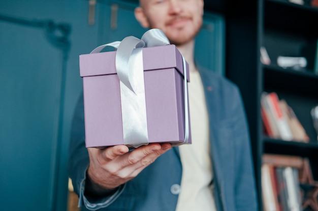 Giftdoos met grijs zilveren lint in de handen van de jonge attracrive mens op blauwe achtergrond
